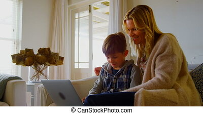Front view of young Caucasian mother and son using laptop on sofa in a comfortable home 4k