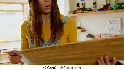 Front view of young caucasian woman examining skateboard ...