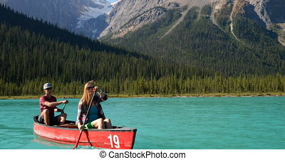 Front view of young couple rowing boat on a turquoise river ...