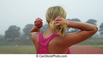 Front view of young female athlete tying her hair at sport venue. She is standing on a running track 4k