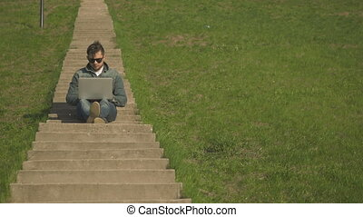 Front View of Young Hipster Man In Sunglasses Sitting On The Stairs Using Laptop