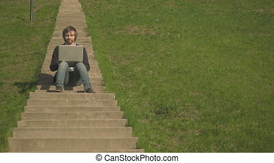 Front View of Young Man Sitting On The Stairs In Park Using Laptop