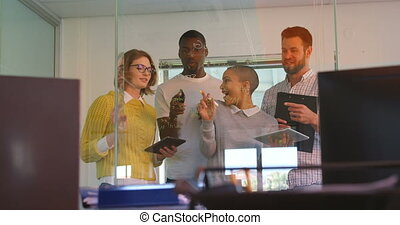 Front view of young mixed race business team discussing over glass wall in modern office 4k