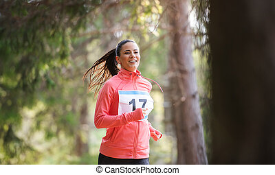 Front view of young woman running a race competition in nature.