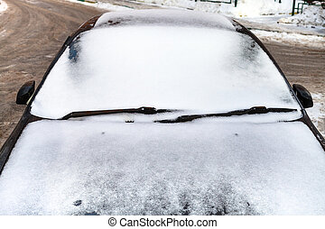 front view on car covered by snow in winter