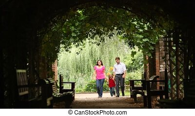Front view on family walk in plant tunnel