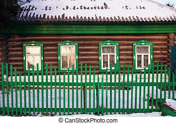 Front view on green log cabin facade in the winter.
