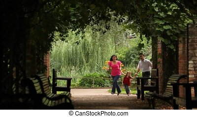 Front view on happy parents with child run in plant tunnel