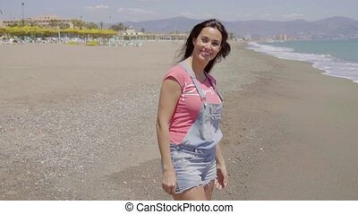 Front view on lady walking along beach - Front view on...