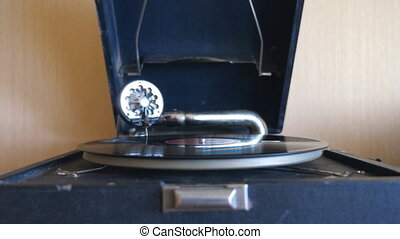 Front view on old playing gramophone. Needle sliding smoothly at black vinyl record spinning on vintage turntable. Retro concept. Slow motion Close up.