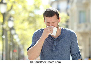 Ill adult man blowing using a tissue in the street