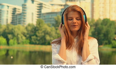 front view redhead girl listen music outdoors - portrait...
