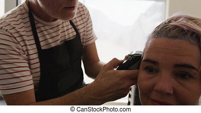Front view woman having her hair cut by a hairdresser - ...