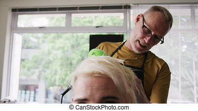 Front view woman having her hair dry by a hairdresser - ...