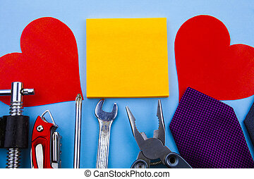 Front view working tools. Wrench clamps screwdriver tie middle note pads two paper hearts good advertisement house repair Fathers Day. Man repairing damages at home