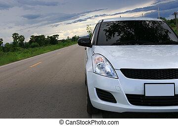 front, von, weißes, auto, parken, auf, der, asphaltstraße, mit, sonnenuntergang, und, schwarz, wolkenhimmel