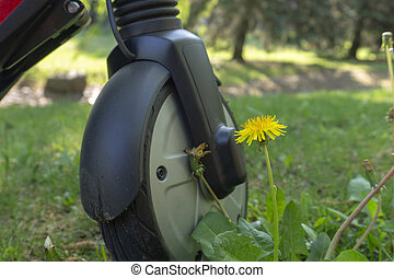 Front wheel of a electric scooter on meadow grass