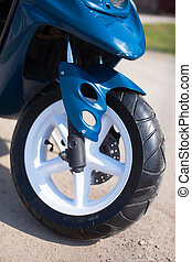 Front wheel of blue modern scooter on the gravel road