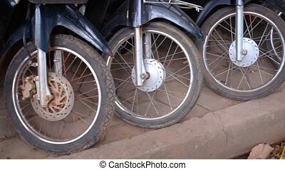 Forks, fenders and rusty spoked front wheels of many motorcycles, parked on a sidewalk along a typical street in Asia.