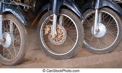 Front Wheels of Many Motorcycles Parked on a Sidewalk in...