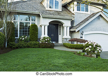 Front yard with rhododendrons in full spring bloom and plush green grass