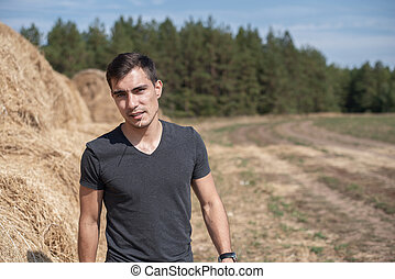 Frontal authentic portrait of a young man in a gray t-shirt on the background of a field with haystacks