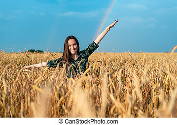 Frontal portrait of a woman in a field with rye spikelets on a rainbow background