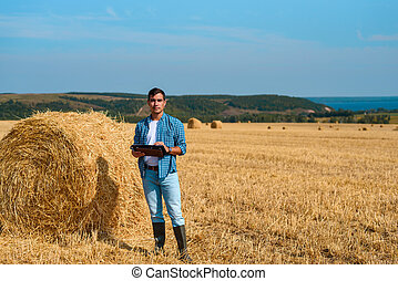 Frontal portrait of man botanist farmer with a tablet in blue jeans and a shirt and a white t-shirt in a field with haystacks