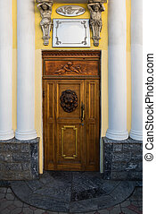 Frontal view of a old red wooden door with yellow house
