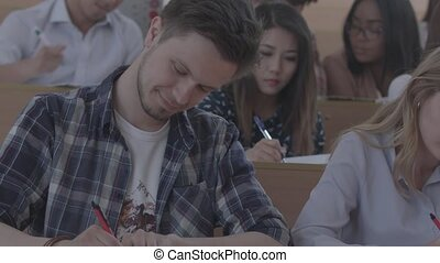 Frontview of a positive learning student writing in notebook , smiling and laughing during the class in university. Other groupmates on background. Wearing colorful casual clothes.