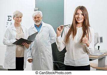 Frontview of satisfied patient smiling in front of old oculist and assistant.