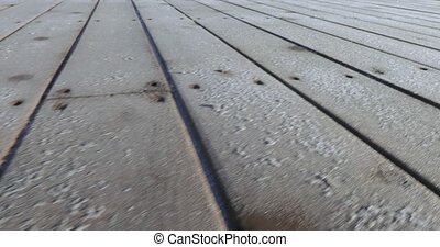 Frost on wooden boards - On the bank of the city pond a...