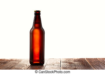 Frosted buttle of light beer on wood table