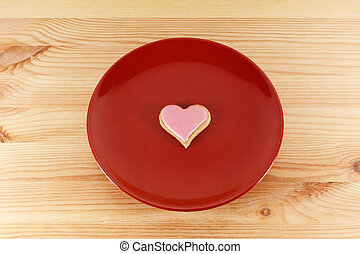 Frosted heart-shaped cookie on a red plate