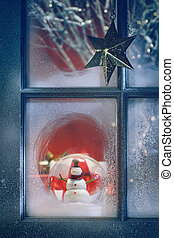 Frosted window with Christmas decoration inside