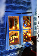 Frosted window with Christmas decorations and festive lights