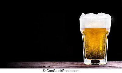Frosty glass of light beer set isolated on a black...