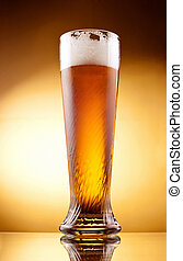 Frosty glass of light beer with froth over yellow background