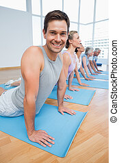 Froup doing cobra pose in row at yoga class