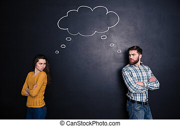 Frowning angry couple thinking identically over background of chalkboard