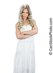 Frowning attractive model in white dress posing