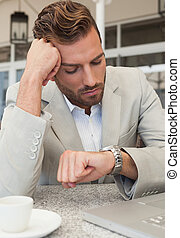 Frowning businessman looking at his watch in patio of restaurant