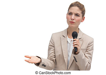 Frowning businesswoman holding microphone on white...