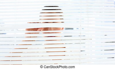 Frowning businesswoman peeking through blinds - Frowning...