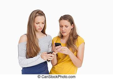 frowning, cellphones, medan, deras, se, kvinnor, två, ung