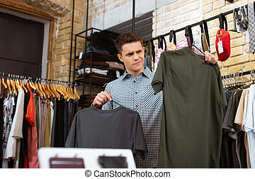 Frowning man feeling not impressed while looking at T shirts