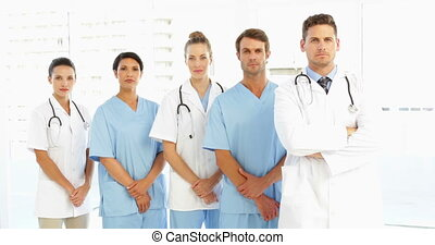 Frowning medical team with hands to