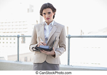 Frowning stylish brown haired businesswoman checking her agenda