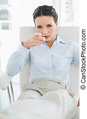 Frowning stylish brunette businesswoman pointing to the camera with her finger in bright office