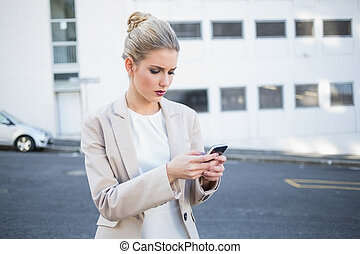 Frowning stylish businesswoman sending a text